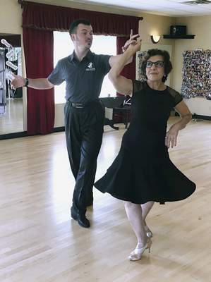 In this Oct. 7, 2019, photo, dance instructor Ned Pavlovic, a native of Serbia, teaches his student Rouhy Yazdani, a native of Iran who now lives in Milford, Conn., some ballroom dance moves at the Fred Astaire Dance Studio in Orange, Conn. (AP Photo/Susan Haigh)