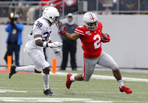 FILE - In this Nov. 23, 2019, file photo, Ohio State running back J.K. Dobbins, right, cuts up field against Penn State defensive back Lamont Wade during the first half of an NCAA college football game, in Columbus, Ohio. Championship weekend crowns the winner of 10 FBS conferences and matches up some big-time players. Wisconin and Ohio State will meet for the Big Ten Championship. (AP Photo/Jay LaPrete, File)