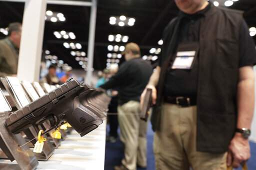 FILE - In this April 27, 2019, file photo, a gun enthusiast looks over the display of pistols in the exhibition hall at the National Rifle Association annual meeting in Indianapolis. The number of background checks conducted by federal authorities is on pace to break a record by the end of this year. (AP Photo/Michael Conroy, File)