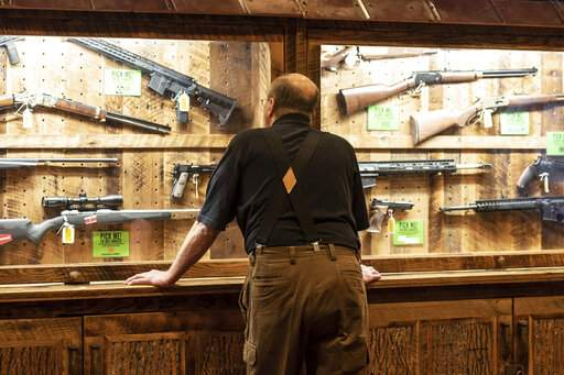 FILE - In this April 25, 2019, file photo, a man looks at cases of firearms in the halls of the Indianapolis Convention Center where the National Rifle Association will be holding its 148th annual meeting in Indianapolis. The number of background checks conducted by federal authorities is on pace to break a record by the end of this year. (AP Photo/Lisa Marie Pane, File)