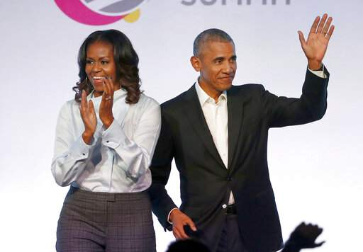FILE - In this Oct. 31, 2017, file photo, former President Barack Obama, right, and former first lady Michelle Obama appear at the Obama Foundation Summit in Chicago. The publisher of Barack and Michelle Obama has pledged to donate 300,000 children's books to a leading educational organization, adding to the 1 million copies already given. (AP Photo/Charles Rex Arbogast, File)