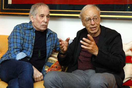 This Nov. 8, 2019 photo shows singer-songwriter, Paul Simon, left, and author-philosopher Peter Singer during an interview in New York to promote the new edition of Singer's book