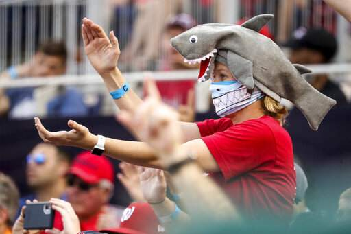 In this Sept. 29, 2019, file photo, a fan wears a shark hat as Washington Nationals' Gerardo Parra comes up to bat in the eighth inning of a baseball game against the Cleveland Indians at Nationals Park in Washington. Creators of the viral video