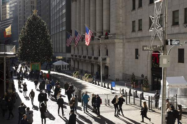 People walk by the New York Stock Exchange, Tuesday, Dec. 3, 2019. Stocks fell broadly Tuesday after President Donald Trump cast doubt over the potential for a trade deal with China this year and threatened to impose tariffs on French goods. (AP Photo/Mark Lennihan)