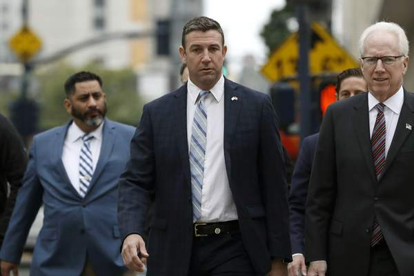 California Republican Rep. Duncan Hunter, center, walks towards federal court Tuesday, Dec. 3, 2019, in San Diego. Hunter said in a TV interview that aired Monday he plans to plead guilty to the misuse of campaign funds at a federal court hearing Tuesday in San Diego. (AP Photo/Gregory Bull)