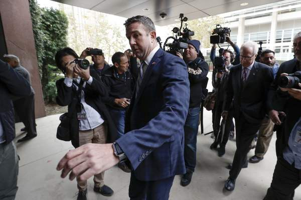 California Republican Rep. Duncan Hunter reaches to open the door to federal court Tuesday, Dec. 3, 2019, in San Diego. Hunter said in a TV interview that aired Monday he plans to plead guilty to the misuse of campaign funds at a federal court hearing Tuesday in San Diego. (AP Photo/Gregory Bull)