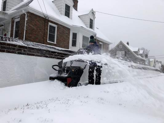 Doreen Goy, of Warwick, R.I., uses a snowblower to clear a sidewalk after a second round of snow struck the area, on Tuesday, Dec. 3, 2020. (AP Photo/William J. Kole)