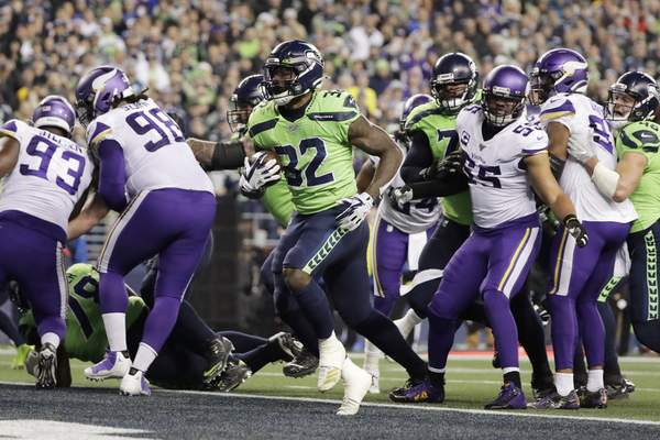 Seattle Seahawks' Chris Carson, center, scores on a run against the Minnesota Vikings during the first half of an NFL football game, Monday, Dec. 2, 2019, in Seattle. (AP Photo/Ted S. Warren)