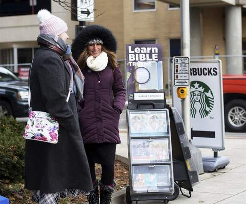 Jehovah's Witnesses' volunteers Korinna Lewellyn, left, and Lori Hughes bundle up Tuesday at one of the free literature stations set up around the city at Jefferson Boulevard and Calhoun Street. (Katie Fyfe | The Journal Gazette)