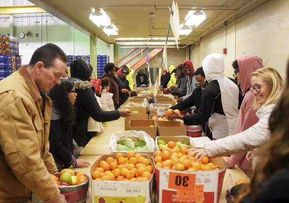 Katie Fyfe | The Journal Gazette Students and staff from FWCS pack items Tuesday at the Bill C. Anthis Center for the district's 30th annual fruit sale that starts Thursday.