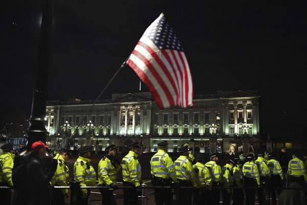 A supporter of President Donald Trump waves the U.S. flag outside Buckingham Palace in London, Tuesday, Dec. 3, 2019. (AP Photo/Alberto Pezzali)