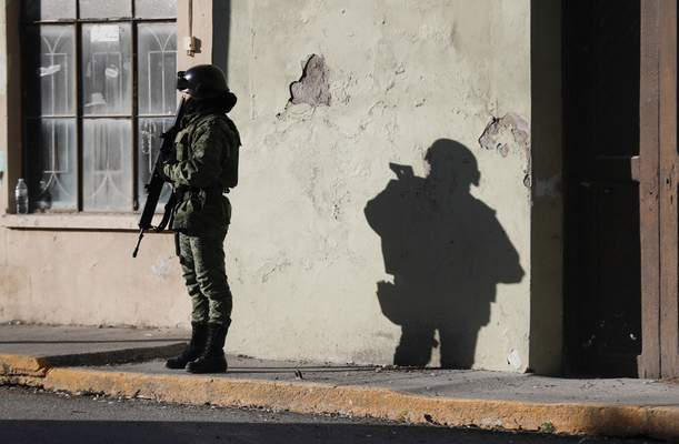 A member of the Mexican security forces stands guard near City Hall in Villa Union, Mexico, Tuesday, Dec. 3, 2019. (AP Photo/Eduardo Verdugo)