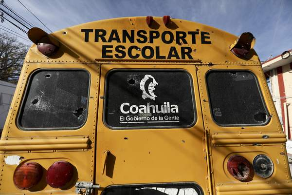 A school bus with bullet holes sits parked outside City Hall in Villa Union, Mexico in Monday, Dec. 2, 2019. (AP Photo/Eduardo Verdugo)