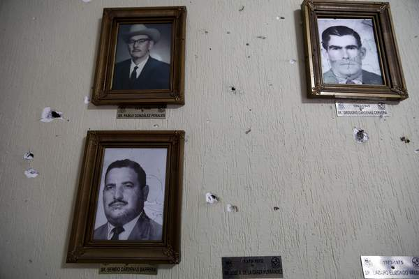 Portraits of former mayors of Villa Union hang on a wall riddled with bullet holes after a gunbattle, inside City Hall, in Villa Union, Mexico, Monday, Dec. 2, 2019. (AP Photo/Eduardo Verdugo)