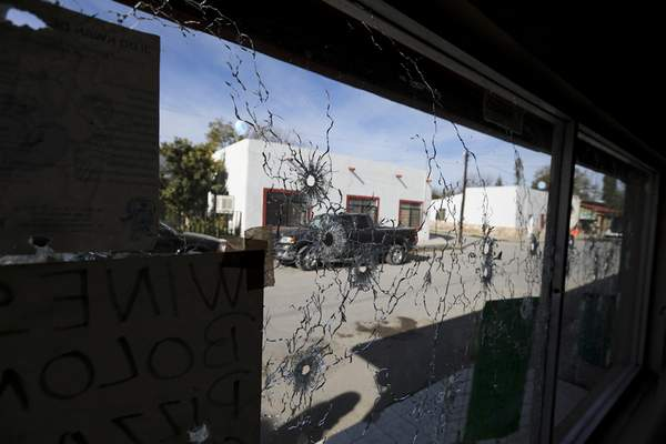 A shop's windows are riddled with bullet holes near City Hall after a gunbattle in Villa Union, Mexico, Monday, Dec. 2, 2019. (AP Photo/Eduardo Verdugo)