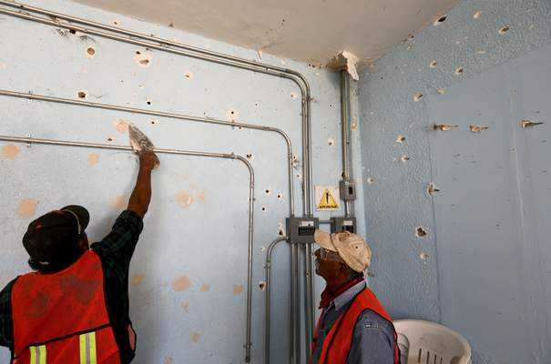 A worker repairs a wall riddled with bullet holes at City Hall in Villa Union, Mexico, Monday, Dec. 2, 2019.  (AP Photo/Eduardo Verdugo)