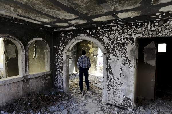 A former policeman walks through an abandoned home, torched by the Zetas cartel eight years back, in Allende, Coahuila state, Mexico, Tuesday, Dec. 3, 2019. (AP Photo/Eduardo Verdugo)