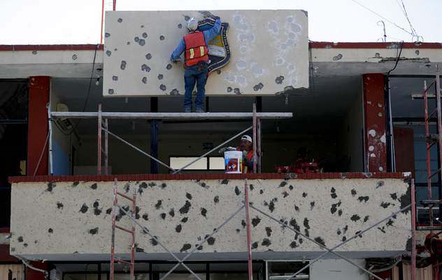 Workers repair the facade of City Hall riddled with bullet holes, in Villa Union, Mexico, Monday, Dec. 2, 2019. (AP Photo/Eduardo Verdugo)