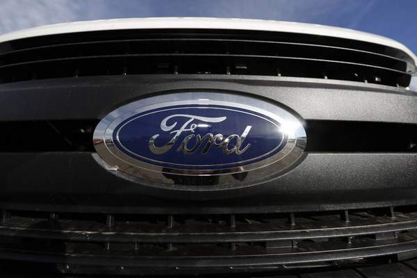 FILE - In this Nov. 10, 2019, file photograph, the company logo shines off the grille of an unsold F-350 pickup truck at a Ford dealership in Littleton, Colo. Ford Motor Co. is recalling nearly 262,000 heavy-duty pickup trucks in the U.S. and Canada because the tailgates can open unexpectedly. The recall covers F-250, F-350 and F-450 trucks from the 2017 through 2019 model years. All the trucks have electric tailgate latch release switches in the tailgate handle. (AP Photo/David Zalubowski, File)