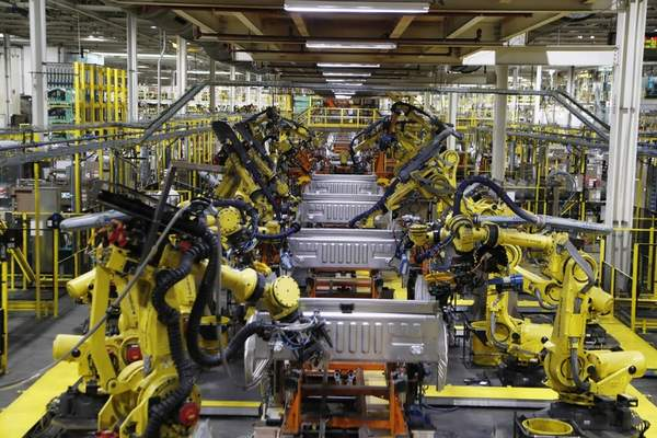 FILE- In this Sept. 27, 2018, file photo robots weld the bed of a Ford F Series trucks on the assembly line at the Ford Rouge assembly plant in Dearborn, Mich. Ford Motor Co. is recalling nearly 262,000 heavy-duty pickup trucks in the U.S. and Canada because the tailgates can open unexpectedly. The recall covers F-250, F-350 and F-450 trucks from the 2017 through 2019 model years. All the trucks have electric tailgate latch release switches in the tailgate handle. (AP Photo/Carlos Osorio, File)