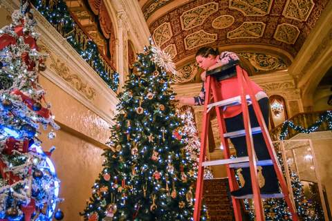 Mike Moore | The Journal Gazette Marley Carden decorates the Pine Hills Learning Place's Christmas tree for the Festival of Trees at the Embassy Theatre on Monday. This year's Festival of Trees will feature 60 uniquely decorated trees and runs from through Dec. 4.