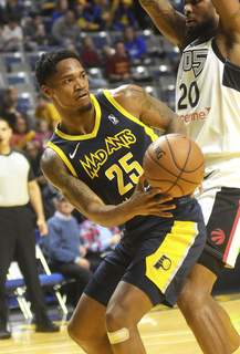 Katie Fyfe | The Journal Gazette  Mad Ants' Travin Thibodeaux passes the ball under the hoop during the second quarter against Raptors 905 at Memorial Coliseum on Saturday.
