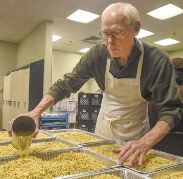 Michelle Davies | The Journal Gazette St. Mary's Soup Kitchen volunteer Mike Rosswurm adds chicken broth to pans of stuffing Wednesday afternoon in preparation for Thanksgiving.