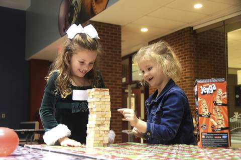 Photos by Katie Fyfe   The Journal Gazette Molly Warner, 6, left, and Alaythea Baker, 6, enjoy a game of Jenga on Sunday during North Side High School's 33rd annual Christmas party for Kids Surviving Cancer.