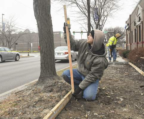 Michelle Davies | The Journal Gazette Cody Waterman with Sierra Construction checks the angle of a sidewalk along Lafayette Street on Tuesday morning.