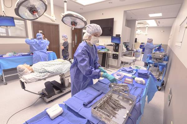Students in Trine University's surgical technology program practice setting up for a procedure in one of the surgical suites at Trine's Health Sciences Education Center in Fort Wayne. The suites were part of an 8,900-square-foot expansion to the education center that opened this fall. (Photo by Dean Orewiler / Trine University)