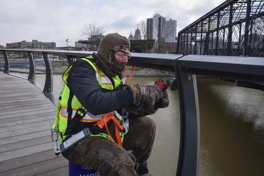 Mike Moore   The Journal Gazette Steve Hickman with Custom Rail Installations uses a grinder Wednesday to remove burrs from metal railing recently installed on the Treetop Canopy Trail at Promenade Park. (The_Journal_Gazette)