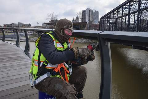 Mike Moore | The Journal Gazette Steve Hickman with Custom Rail Installations uses a grinder Wednesday to remove burrs from metal railing recently installed on the Treetop Canopy Trail at Promenade Park. (The_Journal_Gazette)