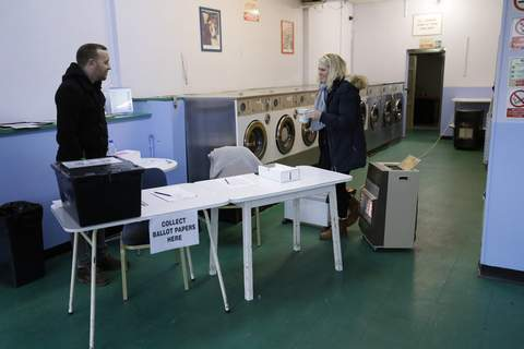 Britain Brexit Election Associated Press: A presiding officer and a clerk stand with heaters to keep warm inside their polling station at Ace Launderette in Oxford, England, on Thursday.