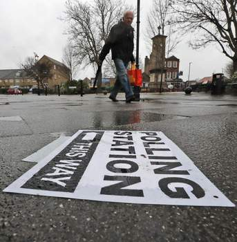Britain Brexit Election A polling station signpost lies on the pavement as voters approach a polling station in Twickenham, England, Thursday, Dec. 12, 2019. (AP Photo/Frank Augstein) (Frank Augstein STF)