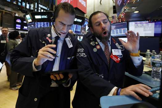 Financial Markets Wall Street FILE - In this Dec. 5, 2019, file photo, trader Gregory Rowe, left, and specialist Michael Pistillo work on the floor of the New York Stock Exchange. (AP Photo/Richard Drew, File) (Richard Drew STF)