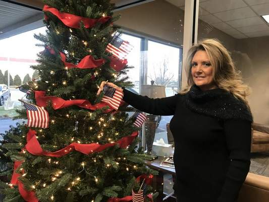 Photos by Jamie Duffy | The Journal Gazette Angela Fields, executive minister at Taylor Chapel, adds another flag to the congregation's tree in honor of four military families the congregation will support with gifts this year.