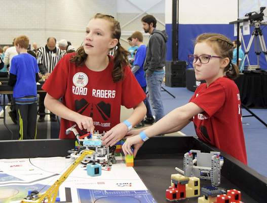 Katie Fyfe | The Journal Gazette  Maggie Zielinski, 12, left, and Audrey Zielinski, 10, show their Lego robot they designed and programmed to the judges during the20th edition of the FIRST LegoLeague's Northern Indiana ChampionshipatPurdue University Fort Wayne.