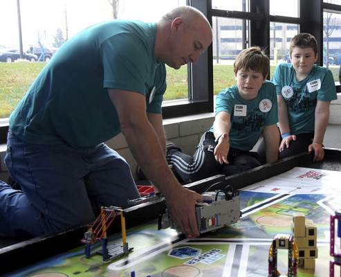 Katie Fyfe | The Journal Gazette  Parker Polfer, center, and Nathan McMinn from Saint Maria Goretti School in Westfield test out their Lego creation before showing the judges during the20th edition of the FIRST LegoLeague's Northern Indiana ChampionshipatPurdue University Fort Wayne on Saturday.