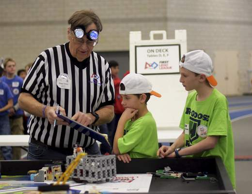 Katie Fyfe | The Journal Gazette  Referee Doug Tanner, left, talks to Owen McNally, center, and Henry Brown about their Lego robot Saturday during the20th edition of the FIRST LegoLeague's Northern Indiana ChampionshipatPurdue University Fort Wayne.