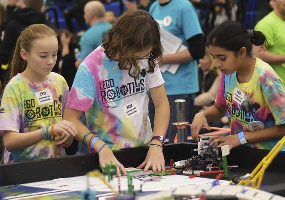 Katie Fyfe | The Journal Gazette  Competitors, from left, Charolette Regan, Jenna Krieg and Keya Patel prepare their Lego robot Saturday to show to the judges during the20th edition of the FIRST LegoLeague's Northern Indiana ChampionshipatPurdue University Fort Wayne.