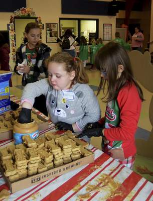 Katie Fyfe | The Journal Gazette  Emersyn Philebamb, 6, left, and Maura Level, 9, make holiday treats for the dogs at Fort Wayne Animal Care & Control during the Deck the Howls event Saturday.