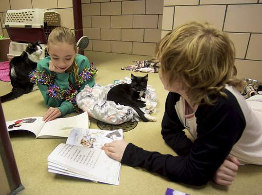 Katie Fyfe | The Journal Gazette Gabriella Stroh, 10, and Sammy Walker, 10, left to right, read to cats during the Deck the Howls event where kiddos get to help get the shelter animals in the holiday spirit while wearing their favorite jammies at Fort Wayne Animal Care & Control on Saturday, December 14th, 2019. refer to story on 1C