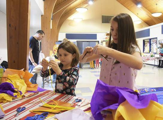 Katie Fyfe | The Journal Gazette  Rowan Miller, 6, left, and Olivia Lawrence, 9, make flowers together Saturday at one of the craft stations during the Deck the Howls event.