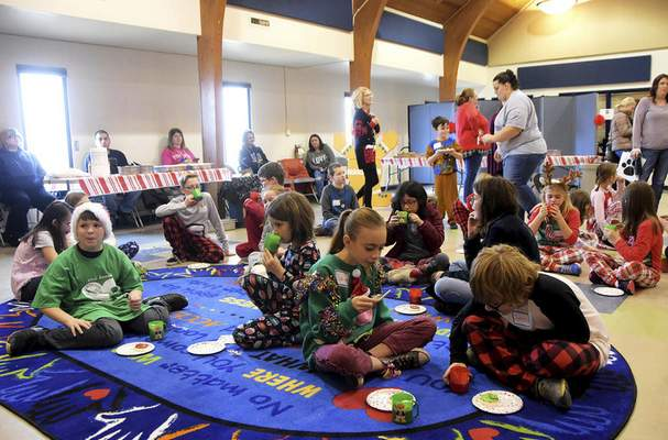 Katie Fyfe | The Journal Gazette  Kids take a break from volunteering and enjoy some hot cocoa and treats during the Deck the Howls event at Fort Wayne Animal Care & Control.Children were invited towear their favorite holidaypajamas whilereading stories to the shelter pets, creating fun toys, designing holiday decorations for kennels, and making holiday treats for the dogs.