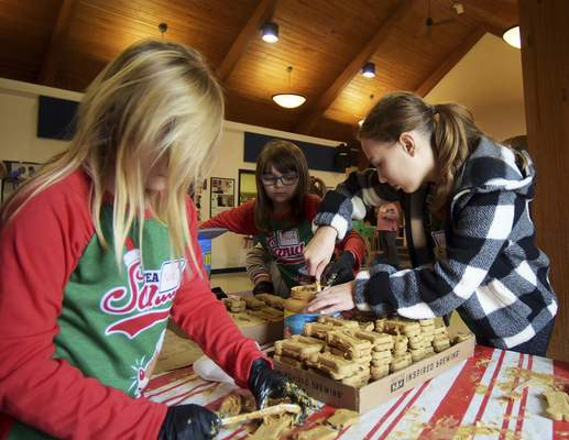 Katie Fyfe | The Journal Gazette  Volunteers, from left, Nola Short, 8, Maura Level, 9, and Adele Freistroffer, 10, make holiday treats for the dogs at Animal Care & Control during their Deck the Howls event on Saturday.