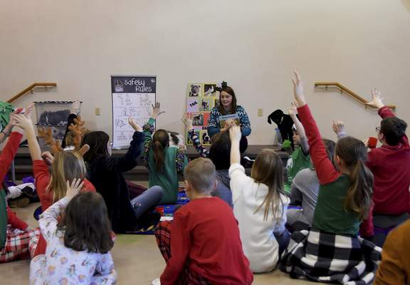 Katie Fyfe | The Journal Gazette  Volunteers eagerly raise their hands to answer questions during story time at Fort Wayne Animal Care & Control during their Deck the Howls event.