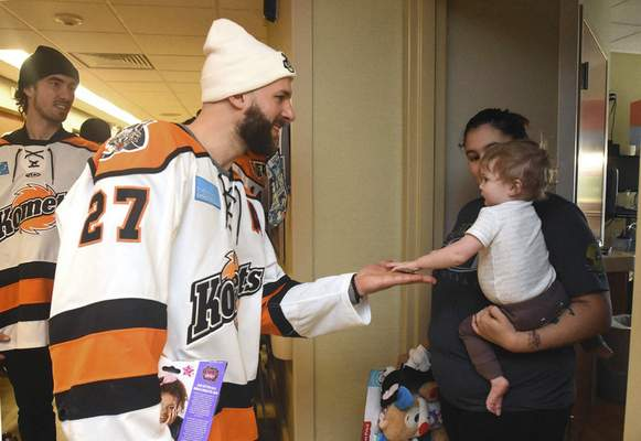 Michelle Davies | The Journal Gazette Shawn Szydlowski, with the Komets, gets a high five from Kole Helvie, 1, of Columbia City, being held by mother Jordan Steinbacher, at Parkview Women's & Children's Hospital Thursday afternoon. The Komets presented Christmas gifts to patients at the unit.