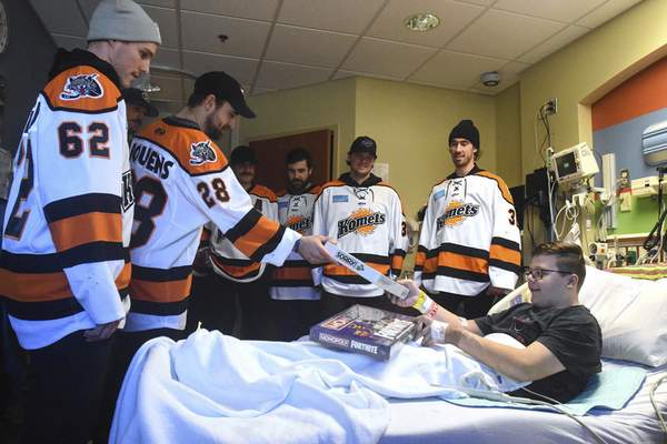 Michelle Davies | The Journal Gazette Matt Boudens, with the Komets, gives a gift to Chase Cashdollar, 14, at Parkview Women's & Children's Hospital Thursday afternoon.