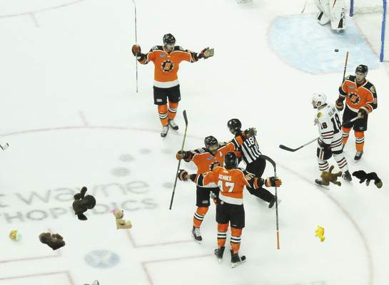 Justin A. Cohn | The Journal Gazette  Komets forward A.J. Jenks, bottom, celebrates with Shawn Szydlowski as stuffed animals rain down from the stands for the annual Teddy Bear Toss.