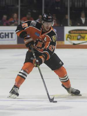 Katie Fyfe | The Journal Gazette  The Komets' A.J. Jenks pushes the puck forward during the second period against the Indy Fuel at Memorial Coliseum on Friday.